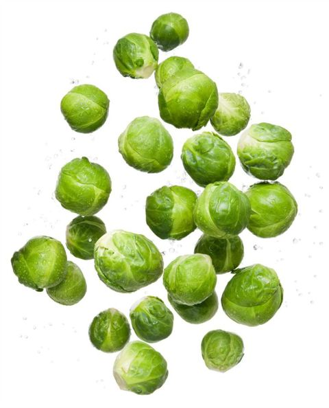 Zdravo eating clean organic fresh vegetable brussel sprouts flying and bouncing up into the air in studio on a white background for wellness